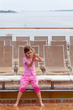 Girl plays with water on deck of ship. Stock Photography