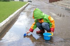 Girl plays with water by pail and shovel. Little girl plays with water by pail and shovel after rain Stock Photo