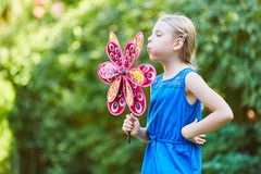 Girl plays with windmill Stock Images