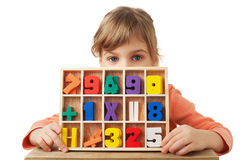 Girl plays in wooden figures in form of numerals Stock Image