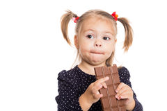 Girl with pleasure eats chocolate Stock Photos