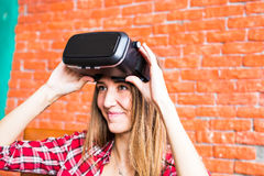 Girl with pleasure uses head-mounted display Royalty Free Stock Photography