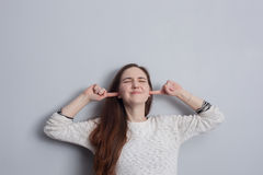 Girl plugs her ears with her hands. Royalty Free Stock Photo