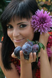 Girl with plums and flowers Royalty Free Stock Photos