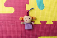 Girl plush toy on a colorful puzzle background Stock Image