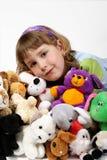 Girl and plushy toys Stock Image