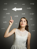 Girl pointing at arrow. Royalty Free Stock Photo