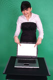Girl pointing at blank laptop screen. Girl pointing at blank laptop screen on green background stock photos
