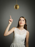Girl pointing at Christmas ball. Stock Photos