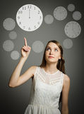 Girl pointing at a clock. Stock Photography