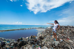 Girl pointing far away standing at the top of trash mountain at garbage dump Royalty Free Stock Photography