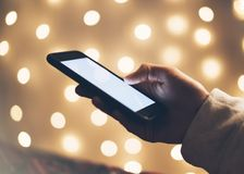 Girl pointing finger a black smartphone with a empty blank screen monitor on the background bokeh light in a homely atmosphere. Freelancer hipster working at stock image