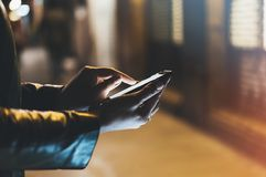 Girl pointing finger on screen smart phone on background illumination color light in night atmospheric city, hipster using. In female hands and text mobile royalty free stock images