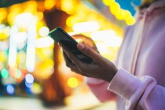 Girl pointing finger on screen smartphone on background bokeh light in night atmospheric city illumination in evening street defoc. Us, hipster using in hands Royalty Free Stock Photos