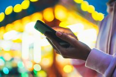 Girl pointing finger on screen smartphone on background bokeh light in night atmospheric city illumination in evening street. Defocus, hipster using in hands stock photos