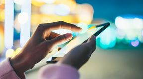 Girl pointing finger on screen smartphone on background bokeh light in night atmospheric city illumination in evening street. Defocus, hipster using in hands stock photo