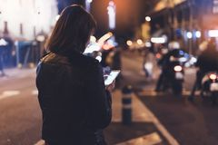 Girl pointing finger on screen smartphone on background bokeh light in night atmospheric city street, blogger hipster girl using stock images