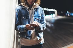 Girl pointing finger on screen smartphone on background illumination bokeh color light in night atmospheric city bridge, hipster u. Sing in female hands and stock photos