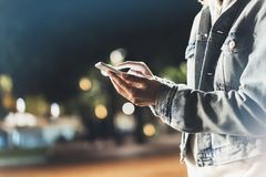 Girl pointing finger on screen smartphone on background illumination bokeh color light in night atmospheric city, hipster using in. Female hands and texting royalty free stock image