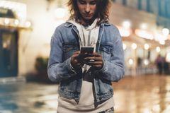 Girl pointing finger on screen smartphone on background illumination bokeh light in night atmospheric city. Hipster using in female hands and texting mobile royalty free stock image
