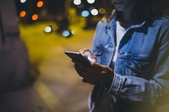 Girl pointing finger on screen smartphone on background illumination glow bokeh light in night atmospheric city, hipster using. In hands mobile phone, mockup stock image