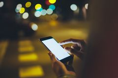 Girl pointing finger on screen smartphone on background illumination glow bokeh light in night atmospheric city, hipster using. In hands mobile phone, mockup royalty free stock photo