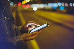 Girl pointing finger on screen smartphone on background illumination glow bokeh light in night atmospheric city, hipster using. In hands mobile phone, mockup royalty free stock photos