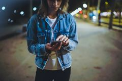 Girl pointing finger on screen smartphone on background illumination glow bokeh light in night atmospheric city, hipster using stock photography