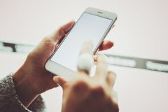 Girl pointing finger on screen smartphone.Female hands texting message mobile phone.Closeup on blurred light coloured stock photo