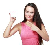 Girl pointing at gift card sign. Young beautiful teen woman showing copy space on empty blank sign or gift card. Portrait of smiling white Caucasian isolated Stock Images