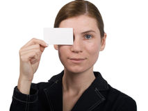 Girl pointing at notecard. The girl specifies in the card on a white background Stock Images