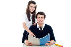 Girl pointing out the answer to her classmate Royalty Free Stock Photo