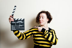 Girl pointing out movie clapper on white background Royalty Free Stock Images