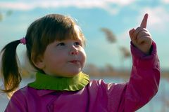 Girl pointing in the sky Stock Photo