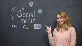 Girl pointing at social media signs on blackboard, addiction to networking stock footage