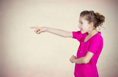 Girl pointing at someone. Closeup side view portrait young, excited, happy girl smiling, laughing, pointing finger towards someone gesture, isolated grey brown Stock Photos