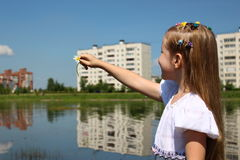 Girl pointing to the distance by the lake. The Girl seven years in a homemade dress Royalty Free Stock Images