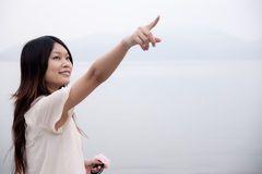 Girl pointing to far away Stock Images