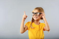 Girl pointing upwards with her index finger Royalty Free Stock Image