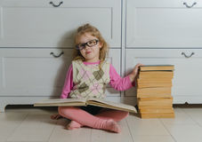 The girl in points with the book sitting on the floor Royalty Free Stock Image