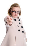 The girl points a finger directly. Girl in coat accuses. isolated over white background Royalty Free Stock Image