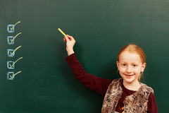 Girl points to the list on the board. Young girl points to the list royalty free stock photo