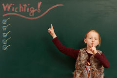 Girl points to the list on the board. Young girl looking up to the chalkboard stock image