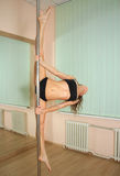 Girl pole dancing in the studio Royalty Free Stock Images