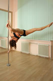 Girl pole dancing in the studio Royalty Free Stock Photos