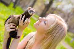 Girl with a polecat. Portrait of the girl with a domestic polecat on hands royalty free stock photo