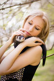 Girl with a polecat. Portrait of the girl with a domestic polecat on hands stock photo