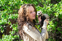 The girl with the polecat in hands Stock Images