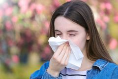 Girl with polen allergy over flowers in early spring. Woman with polen allergy over flowers sneezing in park Stock Photography