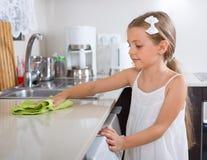 Girl polishing table top at home Stock Photos
